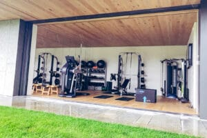 Home gym in the Hamptons with floor to ceiling slider doors opens up to backyard