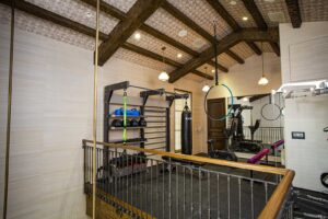 Loft space used for a home gym featuring gym rax suspension, technogym kinesis, pilates, and aerial yoga